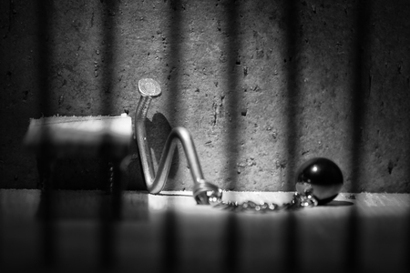 shackle: Conceptual jail photo with iron nail ball and chain behind out of focus bars artistic conversion Stock Photo