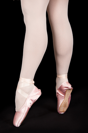 pointes: A ballet dancer standing on toes while dancing on black background artistic conversion Stock Photo