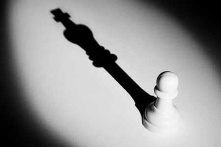 Chess pawn standing in a spotlight that make a shadow of king with darkness actistic conversion