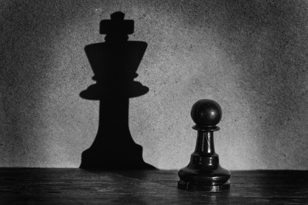 Chess pawn standing in a spotlight that make a shadow of king with darkness actistic conversion photo