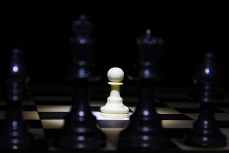 White pawn standing alone in spotlight on chess board between black pieces photo