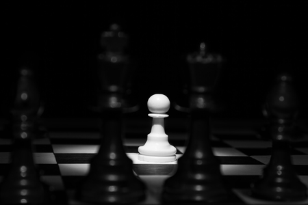 White pawn standing alone in spotlight on chess board between black pieces artistic conversion photo