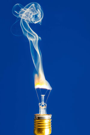 uncontrolled: Broken light bulb burn out with flame on filament with smoke on blue