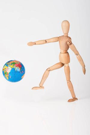 irrespeto: Maniqu� de madera patear un globo del mundo en la falta de respeto aislado en blanco