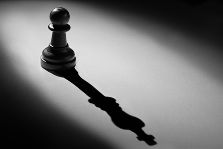 Chess pawn standing in a spotlight that make a shadow of king with darkness photo