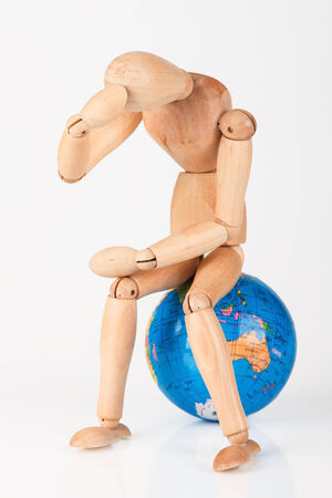Wood mannequin sitting on top of a world globe to protect isolated on white photo