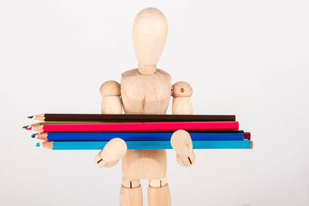 artists dummy: Small wood mannequin standing with bunch of colour pencil isolated on white background