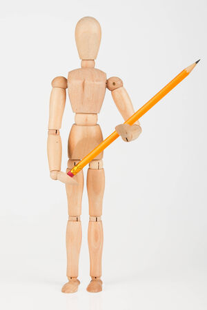 Small wood mannequin standing with colour pencil isolated on white background photo