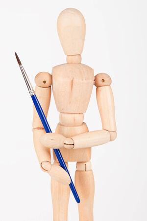 Plain wood mannequin stand upright isolated on white background holding paint brush photo