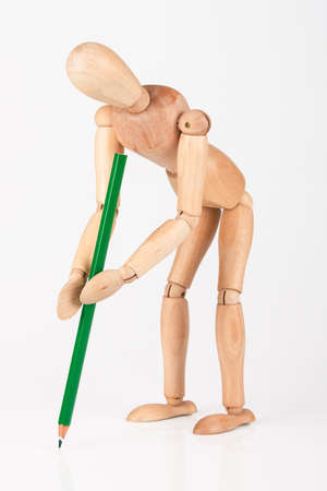 Small wood mannequin stand writing with colour pencil isolated  photo