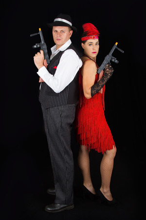 Dangerous bonny and clyde gangster with 1920 style clothes standing with a gun photo