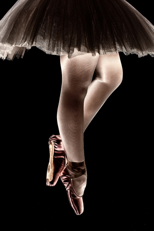black toes: A ballet dancer standing on toes while dancing on black background artistic conversion Stock Photo
