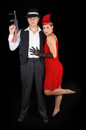 bonny: Dangerous bonny and clyde gangster with 1920 style clothes standing with a gun