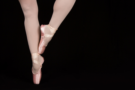 black toes: A ballet dancer standing on toes while dancing on black artistic conversion