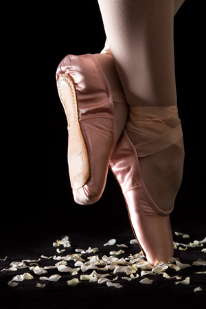 black toes: A ballet dancer standing on toes with rose petals on black