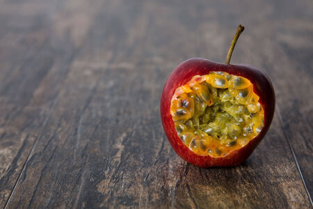 grenadilla: Red apple with bite open passion fruit inside on a wood surface Stock Photo