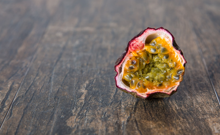 Ripe old passion fruit sliced in halve close-up on brown surface photo