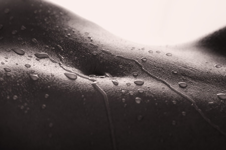 artistic nude: Bodyscape of a nude woman with wet stomach and back lighting in artistic conversion