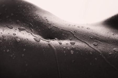 Bodyscape van een naakt vrouw met natte buik en achter verlichting in de artistieke conversie