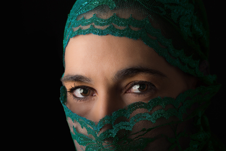 Middle Eastern woman portrait looking sad with a green hijab artistic conversion photo