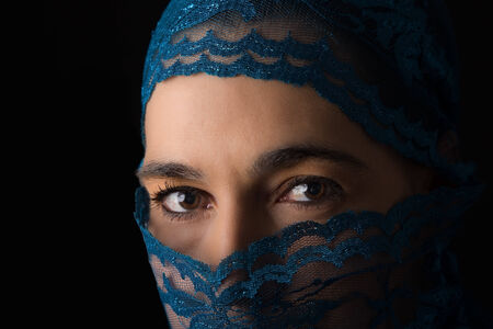 Middle Eastern woman portrait looking sad with a blue hijab artistic conversion photo