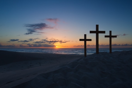 Three crosses on a sand dune next to the ocean with a cloudy sunrise
