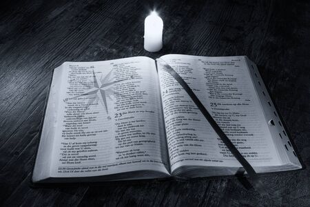 scriptures: Bible with compass on the good message with candle light Stock Photo