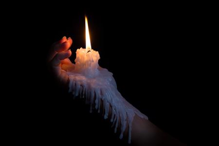 manos abiertas: Abrir mano que sostiene un palillo de la vela con cera que fluye hacia abajo el brazo Foto de archivo