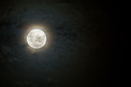 Scary moon on a dark and cloudy night with halo