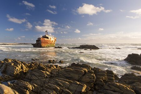boat accident: Old shipwreck long exposure on the rocks at sunset Stock Photo