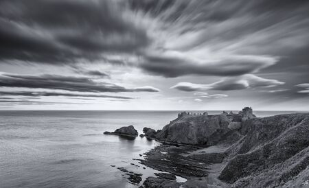 Sunset at Dunnottar Castle on the Scottish coast with moving cloud in black and white