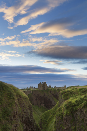 dunnottar castle: Sunset at Dunnottar Castle on the Scottish coast with moving cloud Stock Photo