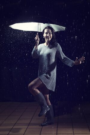 Beautiful woman with silver dress dancing in rain under a black umbrella at night