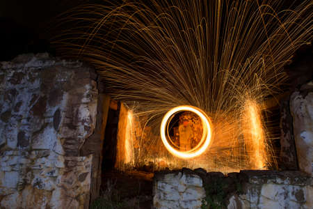 Light painting in an abandon house with spinning steel wool making fire Stock Photo