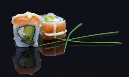 Sushi arranged on a shiny black surface looking very delicious
