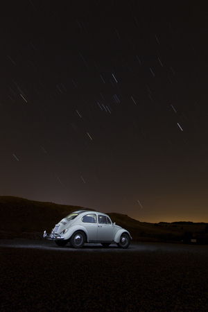 Volkswagen beetle painted with light and startrails in the background
