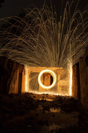 steel wool: Light painting in an abandon house with spinning steel wool making fire Stock Photo