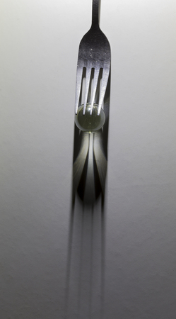 Image of a fork and small glass ball to make a shadow from spotlight