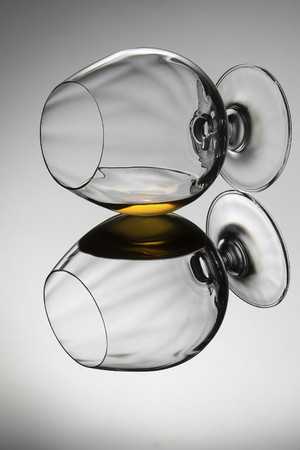 Brandy in a cognac glass lying on its side on a shiny surface with reflection