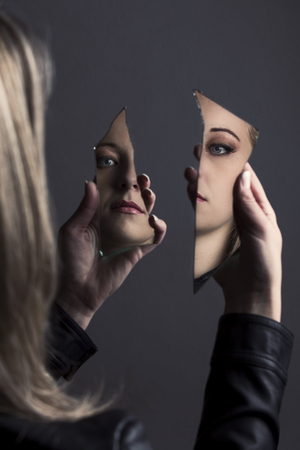 Woman looking at her  own face in two shards of broken mirror Stock Photo