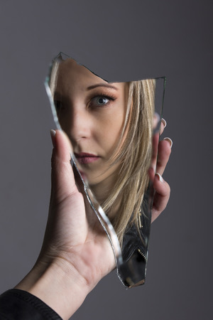 Woman looking at her face in a shard of broken mirror 版權商用圖片