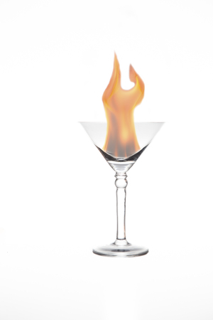 Martini glass with an artificial fire in it isolated on a white background