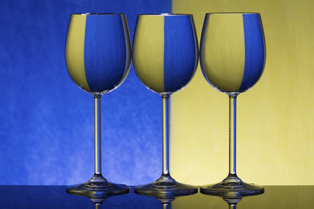 Three wineglasses on a shiny surface with water that distort a yellow and blue background
