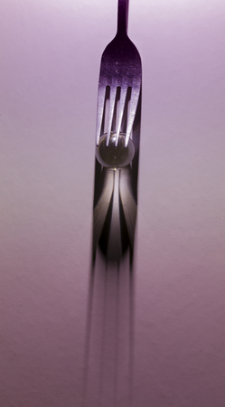 Image of a fork and small glass ball to make a shadow from spotlight on purple background Stock Photo