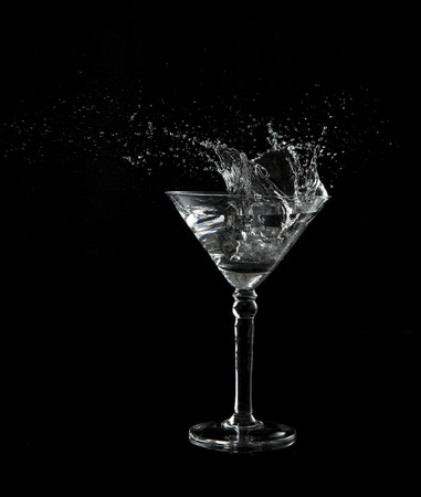 Martini glass low key photo in studio on black background and a water plash