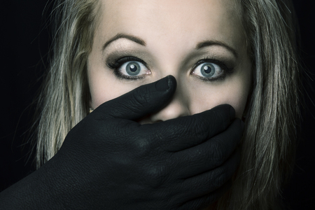 Frightened blonde woman grabbed by black hands on her face in artistic conversion