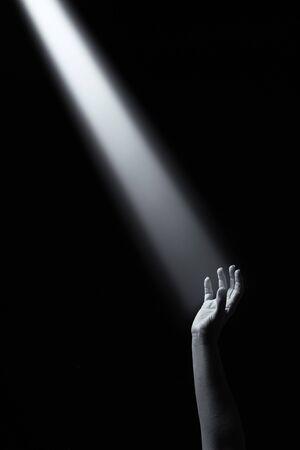 Artistic conceptual monochrome photo of a hand reaching into a beam of light Reklamní fotografie