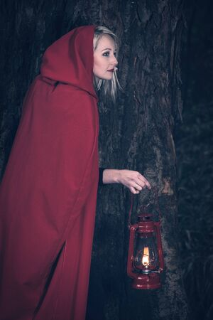 Attractive woman dressed a little red riding-hood walk in a dark forest with a lantern Zdjęcie Seryjne
