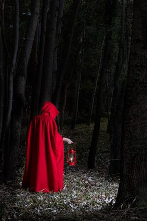 Attractive woman dressed a little red riding-hood walk in a dark forest with a lantern