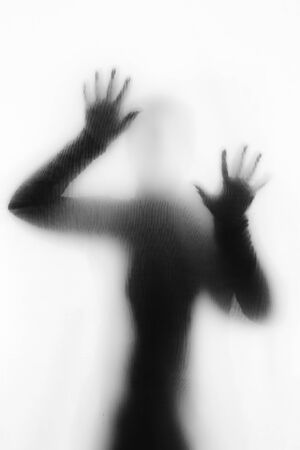 Concept of a frightened woman behind sheet with backlighting in monochrome artistic conversion Stock Photo